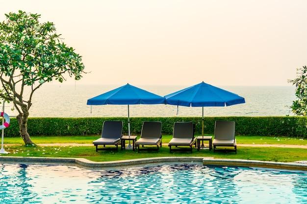 Leżak lub łóżko basenowe z parasolem wokół basenu z zachodem słońca i morzem