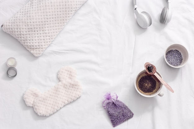 Leżak na płasko ze zdrową ziołową herbatą lawendową w filiżance dla relaksu przed snem. maska do spania i balsam z olejkiem eterycznym na białej pościeli.