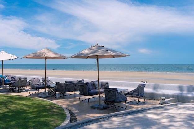 Leżak na świeżym powietrzu i parasol z widokiem na morze z widokiem na plażę z białymi chmurami, błękitne niebo na plaży huahin, tajlandia, wakacje relex w lecie