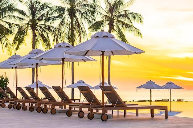 Leżak parasolowy wokół basenu w hotelowym kurorcie z plażą nad morzem i palmami kokosowymi o zachodzie słońca lub wschodzie słońca