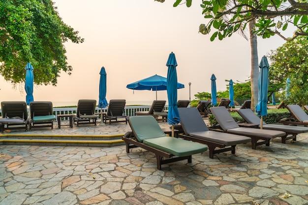 Leżak plażowy lub łóżko basenowe z parasolem wokół basenu z zachodem słońca i morzem w tle