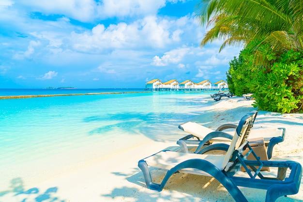 Leżak plażowy z tropikalną wyspą i morzem na malediwach