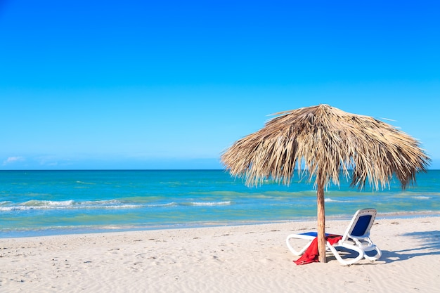 Leżak pod parasolem na piaszczystej plaży nad morzem i niebem.