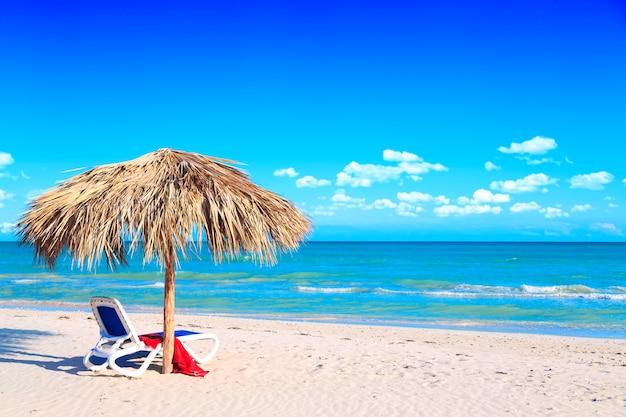 Leżak pod parasolem na piaszczystej plaży nad morzem i pochmurne niebo.