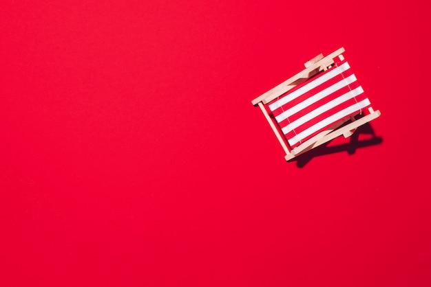 Leżak z twardym cieniem na czerwonym tle papieru.