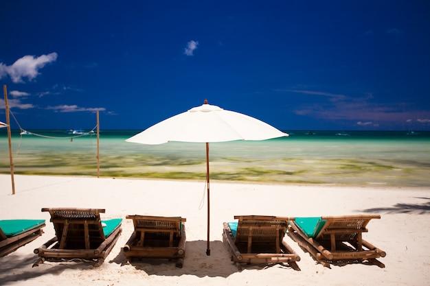 Leżaki i parasol na białej, piaszczystej plaży z widokiem na lagunę