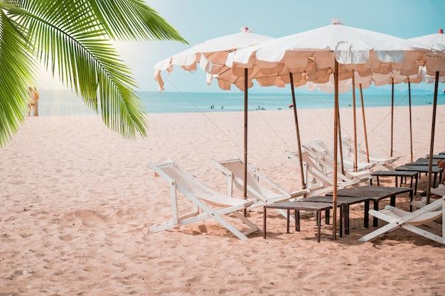 Leżaki i parasol z palmami