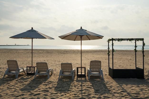 Leżaki i parasole na piaszczystej plaży przeciw morzu i słońcu w chaam, petchaburi, tajlandia