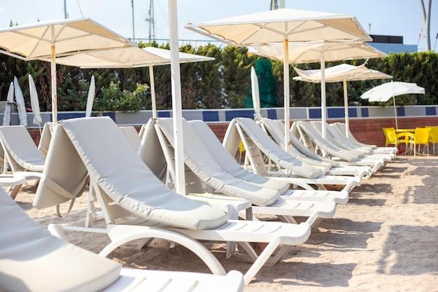 Leżaki i parasole na plaży. na tropikalnej plaży stoją białe leżaki z materacami i parasolami