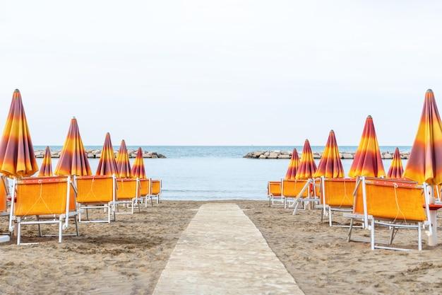 Leżaki i parasole nad brzegiem morza. plaża, morze i parasole w letni dzień.