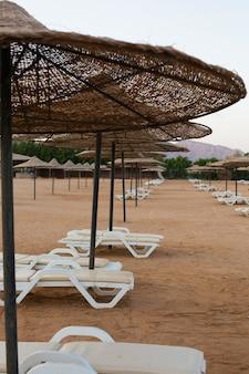 Leżaki i słomiane parasole na pustej plaży