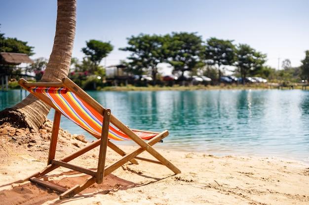 Leżaki na białej, piaszczystej plaży z zachmurzonym błękitnym niebem i słońcem. transparent wakacje tropikalne.