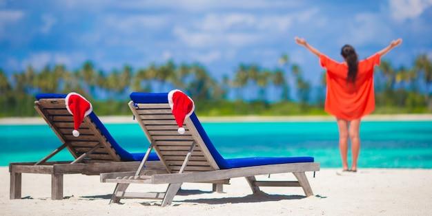 Leżaki na plaży z czerwonymi czapkami santa i młoda kobieta podczas tropikalnych wakacji