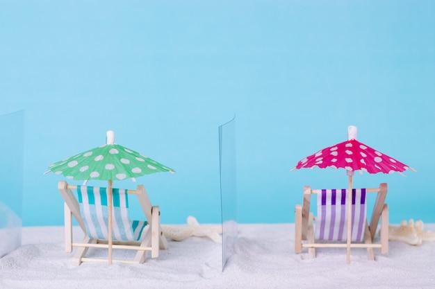 Leżaki oddzielone szklanymi ściankami działowymi na tle piasku