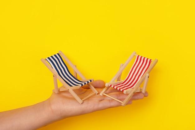 Leżaki plażowe pod ręką, koncepcja wakacji letnich, leżaki na żółtym tle