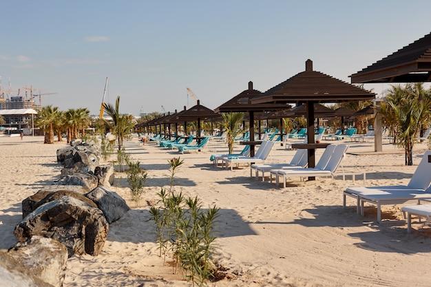 Leżaki pod brązowymi drewnianymi parasolami stoją na plaży