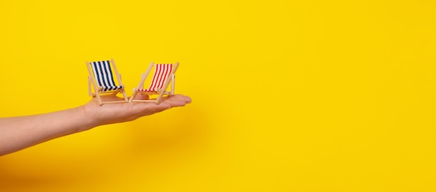 Leżaki pod ręką, tropikalne wakacje, panoramiczny układ na żółtym tle