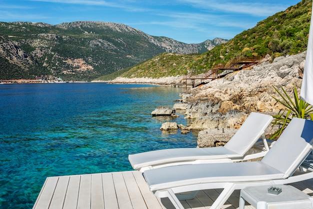 Leżaki z beżowymi materacami na drewnianej podłodze nad turkusowym morzem. luksusowy ośrodek. piękny krajobraz. spokojny odpoczynek. turystyka i podróże.