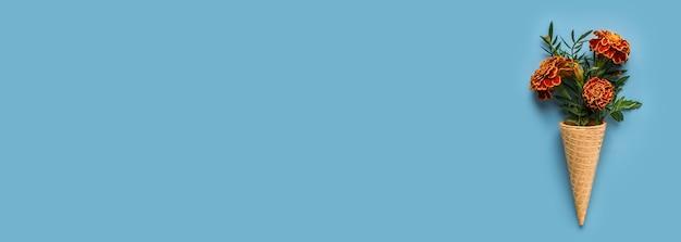 Leżał na płasko ice cream cone z kwiatami nagietka na pastelowy błękit