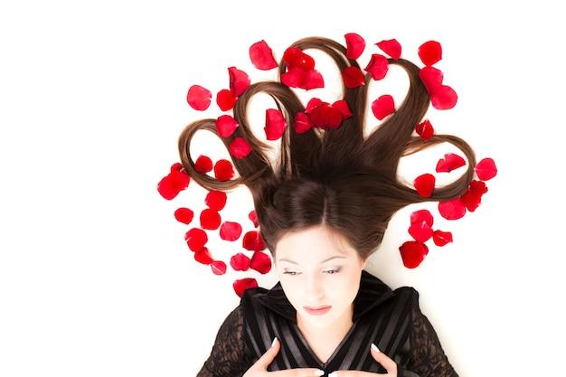 Leżał na płasko młoda brunetka z długimi włosami, leżąc na podłodze z płatkami róż we włosach na białym tle