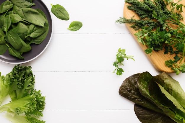 Leżał na płasko z deską do krojenia i miską świeżych liści sałaty ze szpinaku i sałaty, rzymskiej i pietruszki, bazylii. koncepcja zdrowego wegetariańskiego jedzenia.