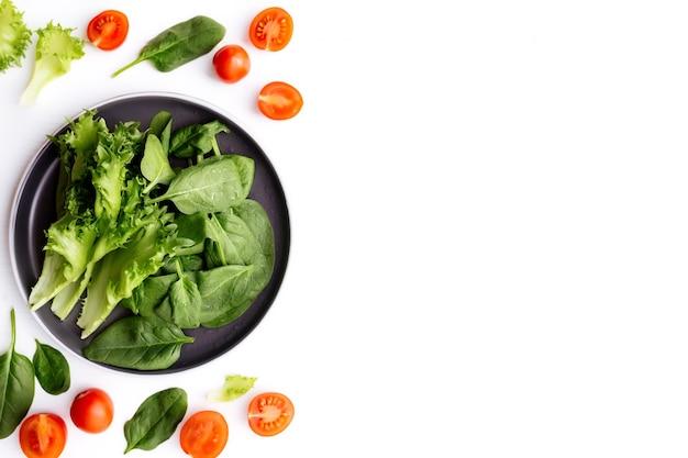 Leżał na płasko z miską świeżych zielonych liści sałaty, sałatą, szpinakiem i czerwonymi pomidorkami cherry, filiżankami i połówkami na białym tle
