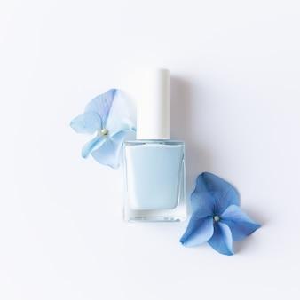 Leżał na płasko z niebieskimi płatkami hortensji z niebieskim lakierem do paznokci w przezroczystej szklanej butelce. naturalna koncepcja manicure i pedicure