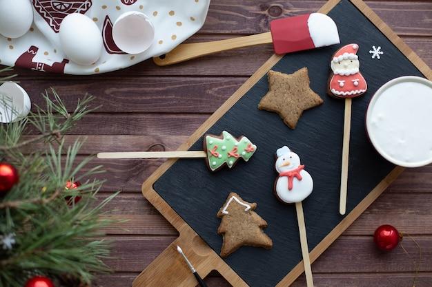 Leżał na płasko z tradycyjnym świątecznym piernikiem. proces domowej dekoracji. kolory noworoczne. zimowe wakacje nastrój i koncepcja rekreacji rodzinnej