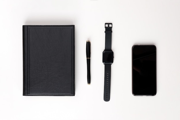 Leżał płasko. czarny skórzany pamiętnik, czarny długopis, elegancki zegarek i telefon na białym tle. widok z góry.