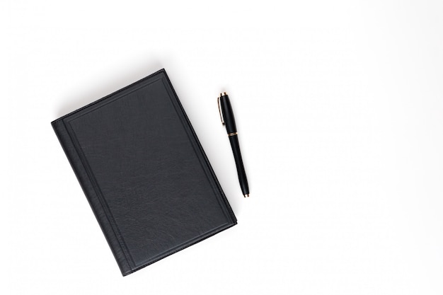 Leżał płasko. czarny skórzany pamiętnik i czarny długopis. widok z góry.
