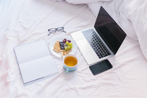 Leżał płasko. herbata w domu w łóżku, sprawdzanie laptopa, czytanie książki i śniadanie. widok z góry