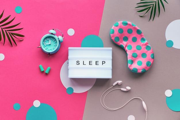 """Leżał płasko, lightbox z tekstem """"sleep"""". koncepcja kreatywnego zdrowego snu. maska do spania, niebieski alarm miętowy, słuchawki, zatyczki do uszu. dwukolorowa różowa srebrna ściana z papierowymi kółkami i liśćmi."""