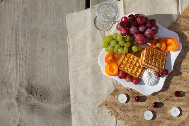 Leżał płasko, martwa natura i zdjęcie jedzenia. piknik na łonie natury w słoneczny dzień. naczynie z owocami i jagodami, goframi i szklanką czystej wody stoi na jutowej tkaninie na drewnianej podłodze ze starych desek