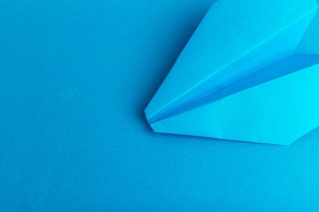Leżał płasko papierowy samolot na pastelowym niebieskim tle