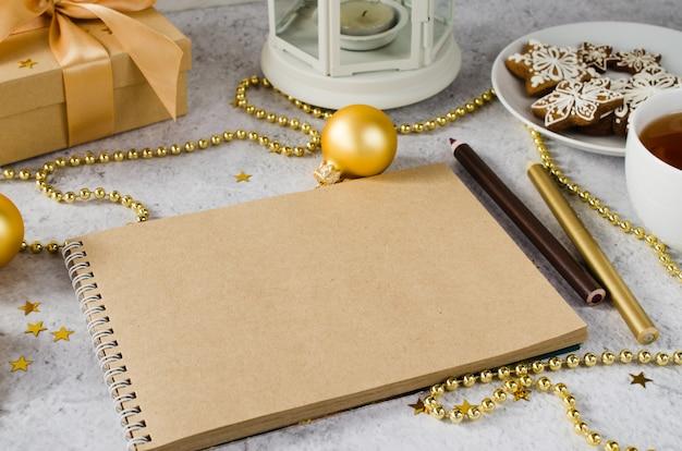 Leżał płasko pusty brązowy notatnik z pudełkiem, herbatą, ciasteczkami i kratą.