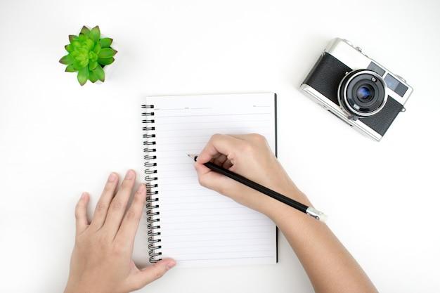 Leżał płasko rysunek dłoni zeszytu, kamery filmowej i doniczki na białym biurku. widok z góry.