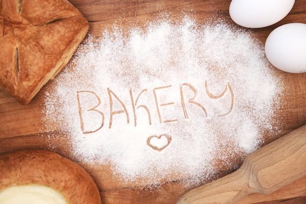 Leżał płasko. składniki do pieczenia na drewnianym tle. przybory kuchenne, wałek do ciasta, jajka, mąka, sernik i ciasto. piekarnia napisana w mące.