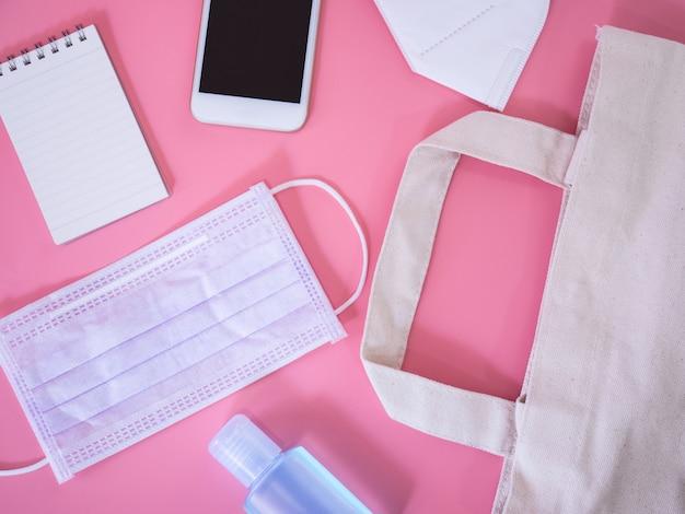 Leżał płasko smartphone, maska chirurgiczna, karta kredytowa, notatnik i żel żel dezynfekujący na różowym tle, widok z góry z miejsca kopiowania tekstu.