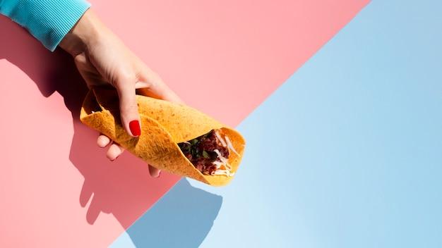 Leżał płasko taco z trzymanym w ręku mięsem i warzywami