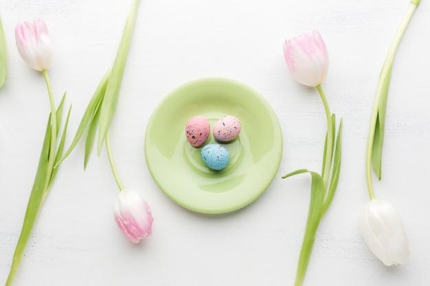 Leżał płasko talerz z kolorowymi pisankami i pięknymi tulipanami
