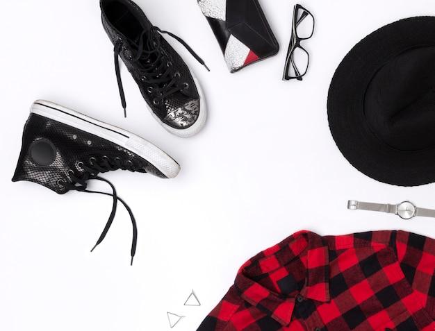 Leżał płasko widok z góry w stylu kobiecym z koszulą w kratę, dżinsy, trampki, zegarki, okulary, portfel, kapelusz i kolczyki