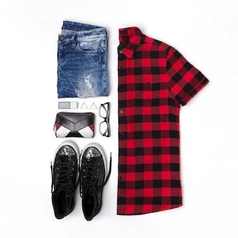 Leżał płasko widok z góry w stylu kobiecym z koszulą w kratę, dżinsy, trampki, zegarki, okulary, portfel, perfumy i kolczyki
