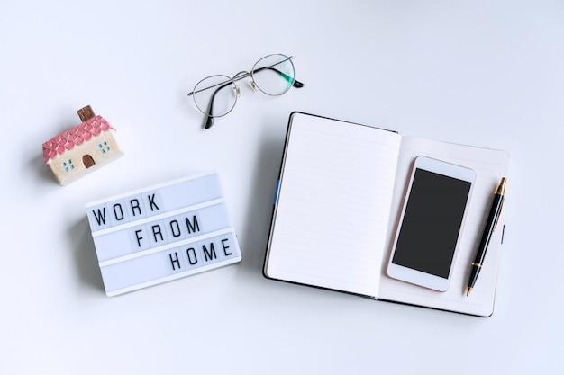 Leżał płasko z białym biurkiem z notatnikiem, okularami i smartfonem