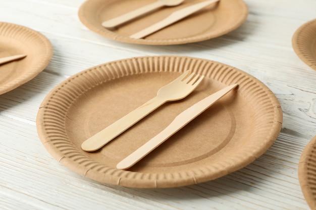 Leżał płasko z ekologicznymi naczyniami na białym drewnianym. naczynia jednorazowe