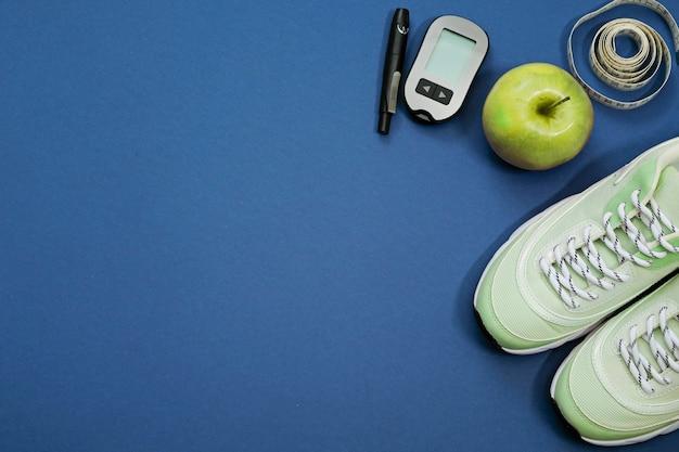 Leżał płasko z koncepcją odchudzania cukrzyca diety. trampki, centymetrem, glukometr na niebiesko