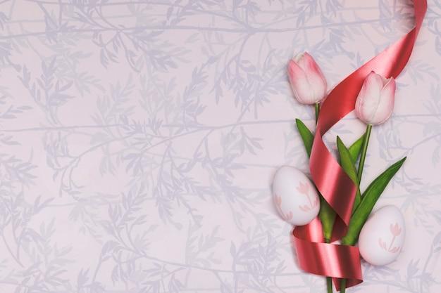 Leżał płasko z tulipanami i czerwoną wstążką