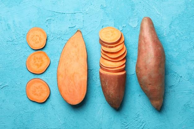 Leżał płasko ze słodkimi ziemniakami na niebieskiej powierzchni