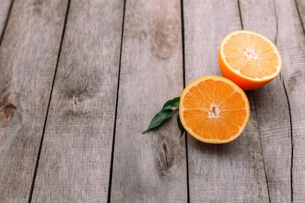 Leżał płasko ze świeżymi dojrzałymi pokrojonymi połówkami pomarańczowych owoców na szarym drewnianym stole. miąższ pomarańczowy i zielone liście. koncepcja zwrotnik żywności. koncepcja zdrowego odżywiania.
