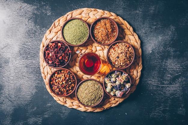 Leżał płasko zioła herbaciane w miseczkach z filiżanką herbaty na drewniane i ciemne teksturowane tło. poziomy