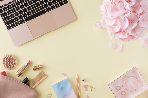 Leżał z płaskim i widok z góry biurka kobiety w domu. kobiece miejsce pracy z laptopem, kwiaty hortensji, akcesoria kosmetyczne, niebieski pamiętnik na pastelowo żółtym tle.